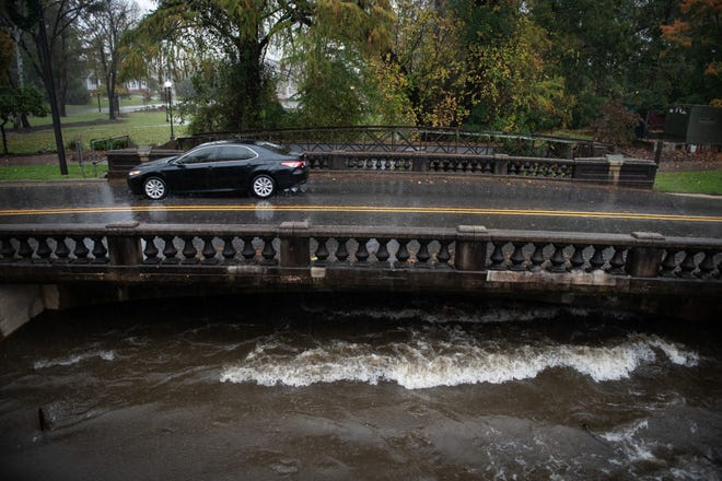 A car drives around barriers to cross a bridge over a swollen Cross Creek on Ray Avenue on Thursday.