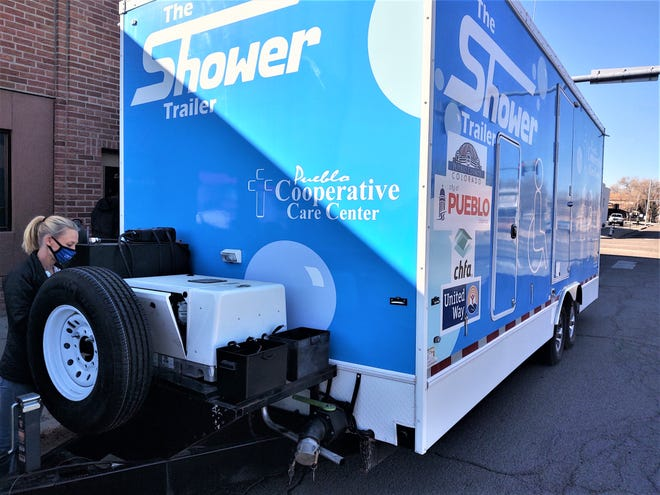 Stephanie Walker, finance manager at Pueblo Cooperative Care Center, checks out the mobile shower's damaged generator Thursday outside the care center.