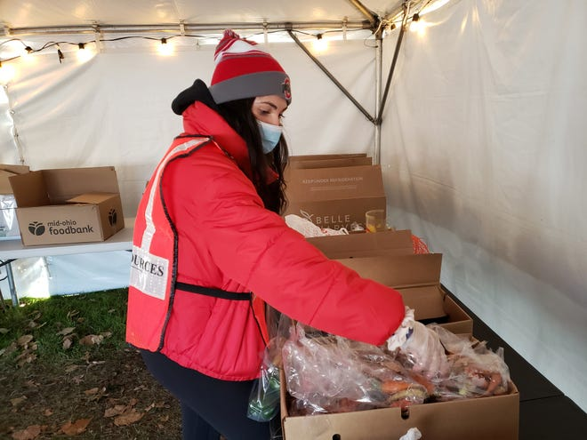 Ohio State University sophomore Maggie O'Brien assembles a bag of vegetables Nov. 12 at the Heart to Heart food pantry. Due to COVID-19 restrictions, the pantry is operating as a drive-thru service at the First Community Church's south campus, 1320 Cambridge Blvd. in Marble Cliff.