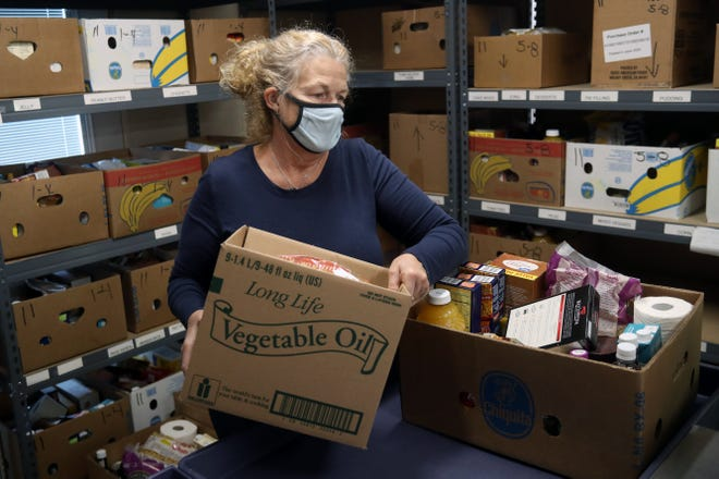 Volunteer Mary Ellen Walsh of Grove City loads a cart with groceries and other supplies for clients at the Grove City Food Pantry on Nov. 11.