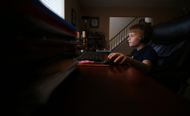 Scottish Corners Elementary School second-grader Charlie McGraw, 8, scrolls through his Dublin City Schools remote-learning site Nov. 10.