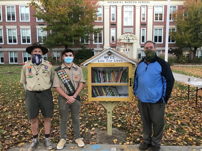 Eagle Scout Luke Camarao stands with his completed Little Free Library outside Nathaniel Morton Elementary School with Scoutmaster John Knox and Principal Michael Spencer.