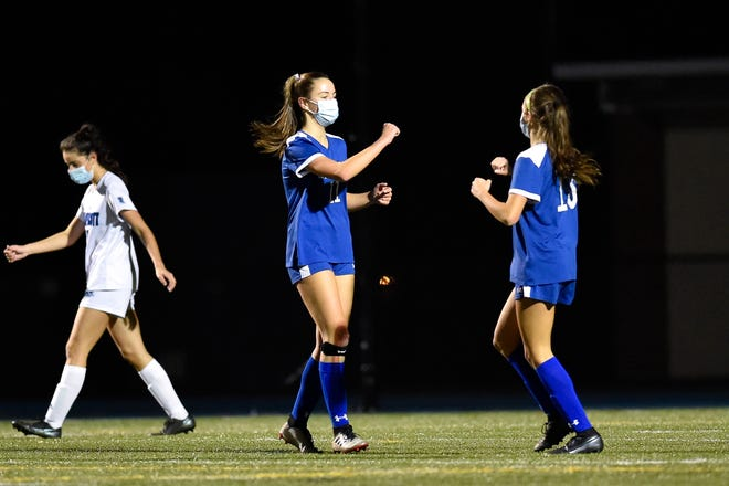 Haley Murphy, left, of Danvers bumps elbows with teammate Riley DiGilio, right, after a goal during a game against Swampscott at Danvers High School on Friday, Nov. 6. [Wicked Local Staff Photo / David Sokol]