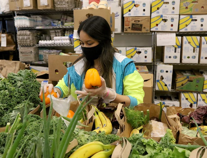 Volunteer Nina Insixiengmay, of Maynard, was adding vegetables to the day's food distribution bags at Open Table, Nov. 12, 2020.