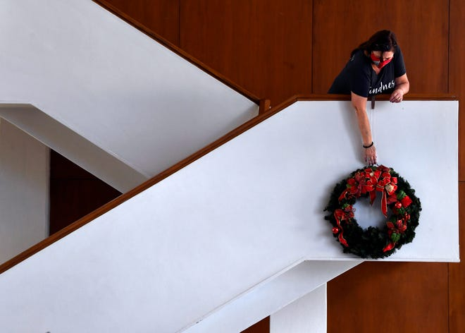 Marta Hanks hangs a wreath on a staircase at the Abilene Convention Center in preparation for the weekend's Christmas in November holiday market Thursday, Nov. 12, 2020.