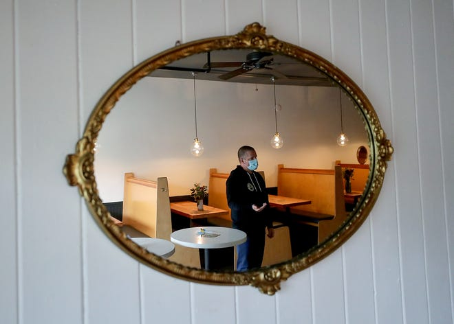 Brendan McGill is reflected in a mirror on the wall as he talks about shifting his long-running flagship restaurant Hitchcock over to a new concept called Burgerhaus, on Bainbridge Island on Thursday, Nov. 12, 2020.
