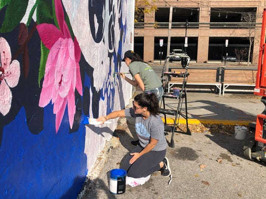 """Artist Jenna Brownlee works painting with her sister Megan Tell and mother Carol Kollings on """"Love Blooms,"""" a new mural in downtown Des Moines."""