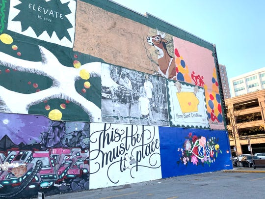 """A new mural, titled """"Love Blooms,"""" joined the collage of artwork displayed at 2nd St. and Court Ave. in downtown Des Moines, replacing a former mural showing The Bachelor star Chris Soules."""