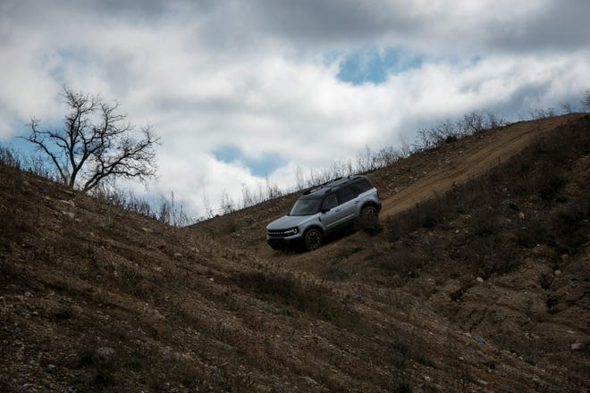 A Ford Bronco Sport drives down a hill at Holly Oaks ORV Park.