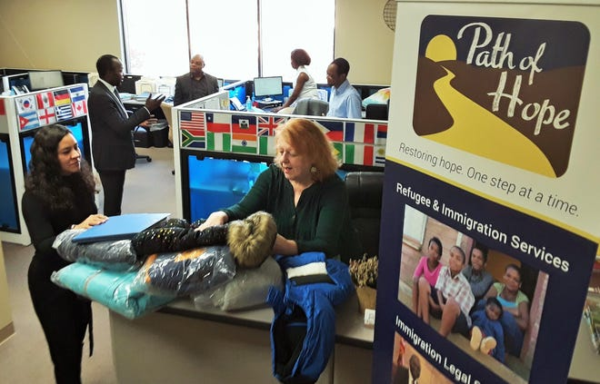 The diverse staff members of Path of Hope work socially-distanced from this flag-adorned Coralville office, serving some 1,600 refugees and immigrants in the Iowa City area.