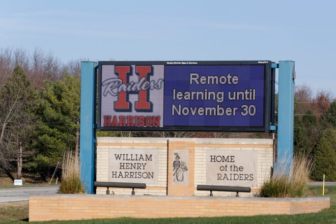 """Remote learning until November 30"" scrolls across a sign outside Harrison High School, Thursday, Nov. 12, 2020 in West Lafayette."