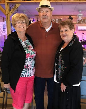 Brenda Donegan, left, with friend Ed Herring  and his partner, Genny Wikgus Funk. Herring recently died from complications from COVID-19.