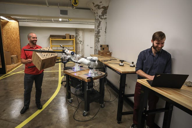 Dextrous Robotics co-founders Evan Drumwright (left) and Sam Zapolsky (right) work inside the company's research lab at Crosstown Concourse in Memphis. It's developing a robot that can handle heavy packages at high speeds.
