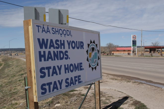 A sign reminds motorists on Arizona Highway 264 in Window Rock, Arizona on March 29 to use precautions to prevent the spread of COVID-19 in communities.