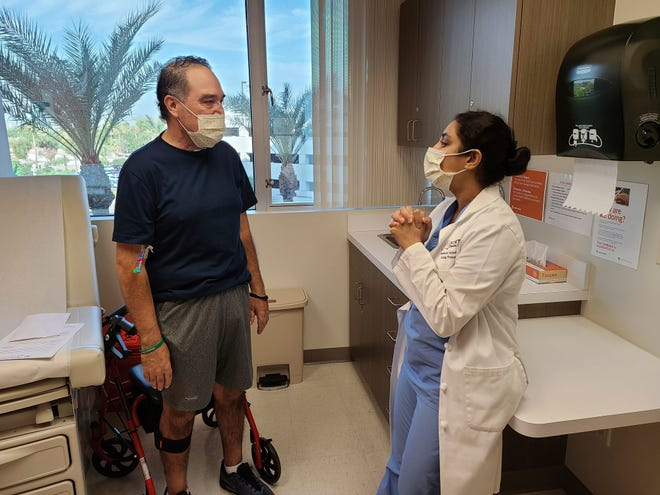In this photo provided by Dignity Health St. Joseph's Hospital, Arthur Sanchez speaks with Dr. Ashwini Arjuna during a follow-up appointment, post-transplant, at St. Joseph's Hospital in Phoenix on Oct. 21, 2020.
