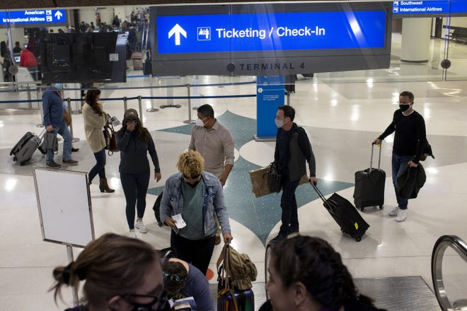 Travelers walk with their luggage at Terminal 4 on Nov. 12, 2020, at Sky Harbor International Airport in Phoenix.