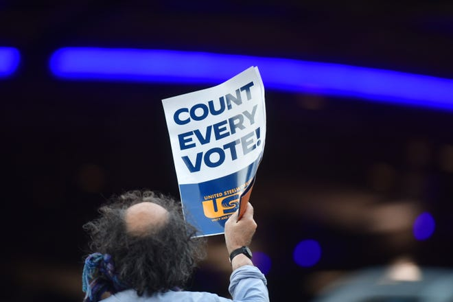 """A man holds a placard that reads """"Count Every Note"""" while demonstrating across the street from supporters of President Donald Trump outside of where votes are still being counted in Philadelphia, six days after the general election on November 9, 2020. (Mark Makela/Getty Images/TNS)"""