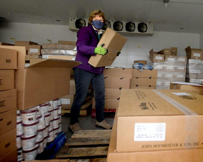 York County Food Bank volunteer Sue Markle of Shiloh moves boxes containing ham in a freezer at the facility Thursday, Nov. 12, 2020. Volunteers will be boxing holiday food on Saturday. Bill Kalina photo