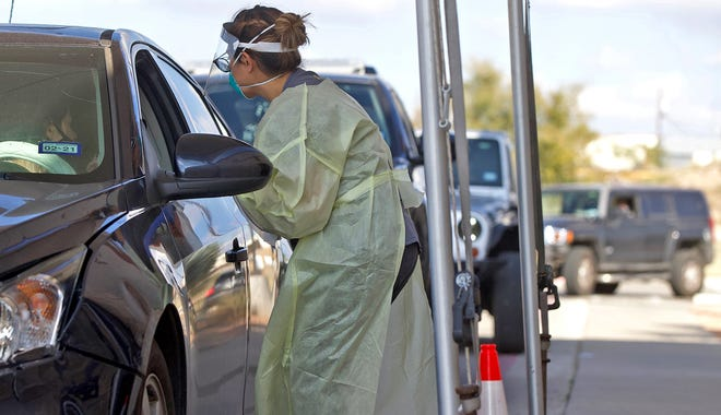 A health care worker at Shannon Clinic North in San Angelo conducts a COVID-19 test at a drive through site Thursday, Nov. 12, 2020.