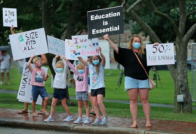 Young elementary school students and their parents attempt to get the attention of passing motorists on Church Street in Winchester, MA on July 30, 2020. A group of Winchester parents hold an event on the town common, voicing their concerns about younger students being able to learn remotely and advocating for the full return of them to classrooms.