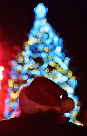 A spectator wearing a Santa Claus hat looks up at the city of Akron's official Christmas tree at Lock 3 Park in, 2018 in Akron, Ohio. (Beacon Journal file)
