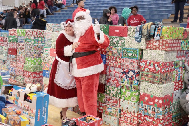 Mrs. Claus and Santa Claus come to help out at a previous Northside Toy Drive distribution at Palo Duro High School. [Neil Starkey / For the Amarillo Globe-News]