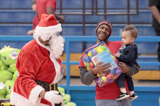 TJ Wilson (1) held by volunteer Dameon Thomas not only received toys but met Santa Claus at a previous Northside Toy Drive distribution at Palo Duro High School. [Neil Starkey / For the Amarillo Globe-News]