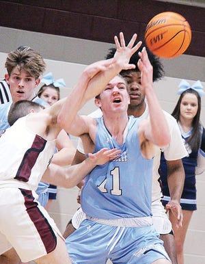 Bartlesville High School forward Adam Nakvinda, center, battles for the ball during basketball action last season.