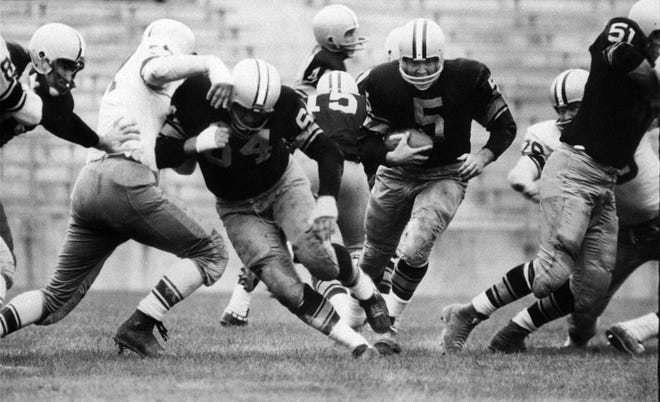 Paul Hornung of the Green Bay Packers carries the ball through the line in an inter-squad game in 1959. Hornung, whose singular ability to generate points as a runner, receiver, quarterback and kicker helped turn them into an NFL dynasty, has died. He was 84.