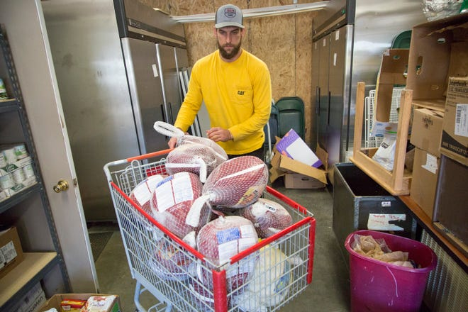 Volunteer Alex Ontiveros loads dozens of frozen turkeys into a shopping cart, preparing them for distribution for Maury County families in need at The Family Center of Columbia on Friday, Nov. 17, 2017.