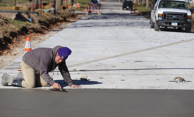 Jobe Ashby, of Burlington, with M.J. Daly Construction, smooths concrete on the north side of the S. 8th and South streets intersection Friday in Burlington. Crews are working on South Street from Fifth Street to Madison Avenue as part of the sewer separation project.
