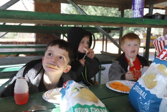 Jordan Ellard, 9, Blake Ellard, 5, and Ryan Reed, 4, devour grilled pork chops during a chilly picnic with family Friday inside the main shelter at Crapo Park in Burlington. They were there with their parents, grandparents and brother Trevor, 7, all from Wayland.