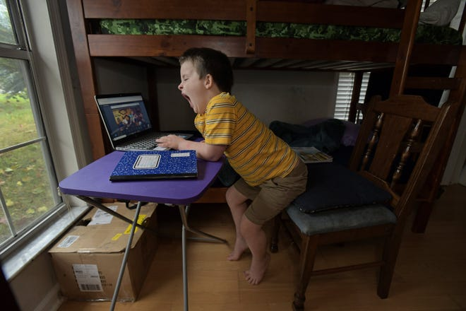 Jordan Dunham yawns as he starts his online school day on a folding table in his bedroom. Annessa Dunham works with her twin sons Jacob and Jordan, 6 as they do distance learning for their first-grade classes from their Ft. Caroline home Friday morning, November 13, 2020. [Bob Self/Florida Times-Union]