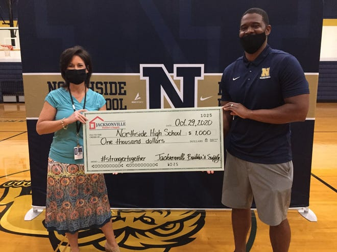 Northside Principal Lynn Jackson, left, and Athletic Director Kendrick Hall hold up a check donated to the school's athletic department from Jacksonville Builder's Supply. [Contributed Photo]