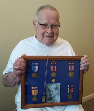 Bob Watson shows a display of his memorabilia from his service in the Army. Watson and Joe Twardzik at Summit Pointsenior living community in Macedonia were honored withinscribed bricks at the Nordonia Hills Veteran Memorial Park.