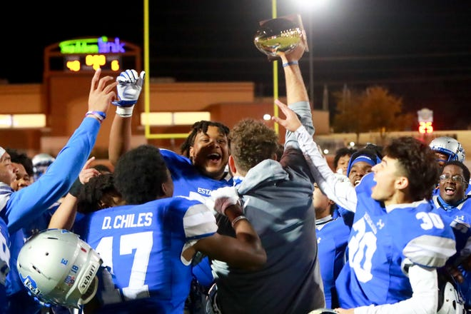 Head coach Joe Cluley brings the trophy to his players after Estacado defeated Pecos 48-6 in a Class 4A Division II bidistrict playoff game Thursday at PlainsCapital Park at Lowrey Field.