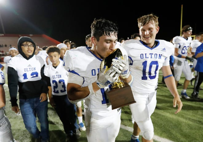 Olton's Aldo Vasquez (11) and Jack Allcorn (10) carry the Class 2A Division I bidstrict trophy off the field after defeating New Deal 35-33 on Thursday at Lobo Stadium in Levelland.