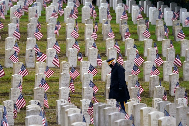 Retired U.S. Army veteran Bill MacCully walks among flag-covered graves in the Veterans Cemetery of Evergreen Washelli Memorial Park on Veterans Day in Seattle.