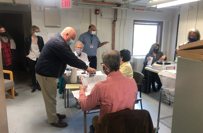 Absentee ballots are being counted at the Ontario County Board of Elections on Nov. 12, 2020. Standing at left in front is Republican Commissioner Michael Northrup. Standing in back in blue-checked shirt is Democratic Commissioner Charles Evangelista.