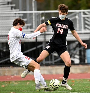Wellesley's Michael Champagne (right) and Natick's Matthew Mela battle for the ball during the first half at Wellesley High School on Tuesday, Oct. 27.