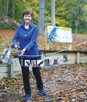 Author Shirley Raines cuts the ribbon for the UT Arboretum's Nature Book Trail, which now has signs based on her book.