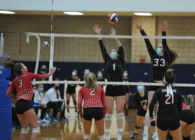 Quincy's Annika Schmitt, center, and Colleen Moran, upper right, leap to block the shot of Hingham's Shea Galko, left, during volleyball action at Quincy High School, Thursday, Nov. 12, 2020.