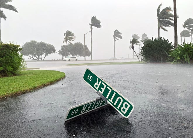 A street sign lies in a parking lot on North Flagler Drive as a squall from Tropical Storm Eta moves over West Palm Beach, Nov. 9, 2020.