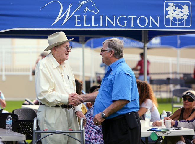 Former county commissioner Ken Adams (left) chats with Wellington planning, zoning, and building director Bob Basehart during a breakfast held at the Wellington Amphitheater December 31, 2015 to kick off the Village of Wellington's 20th anniversary celebration.