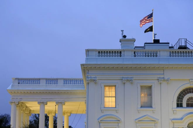 Lights shine from inside the White House at dusk on Wednesday.