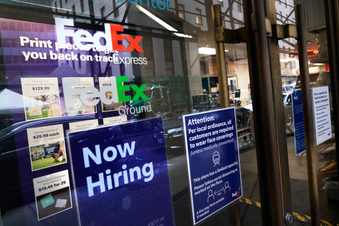 A sign in the window of a FedEx office on Oct. 26 in New York. Carriers like FedEx and UPS are ramping up their holiday hiring while asking store clients to move their shipping volume on lighter days in their network.