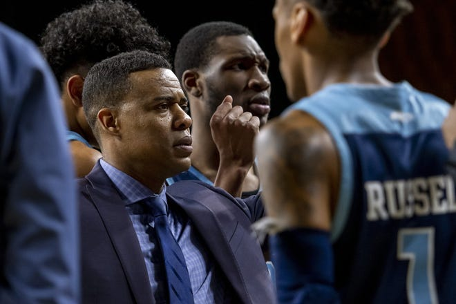 URI head coach David Cox confers with his players during a timeout in a game last season against George Mason.