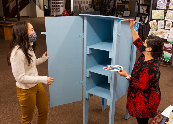 Naomi Saenger, left, watches Sophie Navarro Matchett paint a Little Free Pantry that will soon be installed at the Eugene Family YMCA to provide free food to people in need.