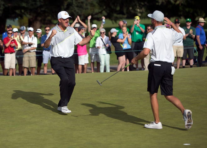 Oregon coach Casey Martin, left, celebrates with Sulman Raza after Raza made the match-winning putt in a semifinal of the 2016 NCAA Championships at Eugene Country Club.