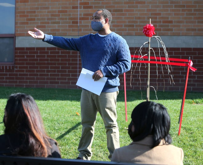 Charles Smith Jr. makes remarks during a tree dedication Friday honoring his late father, Charles Smith Sr., at the Arts Academy at Summit in Canton. In the foreground are Smith Sr.'s daughters, Christian Holcomb (left) and Nakecha Lewis (right).